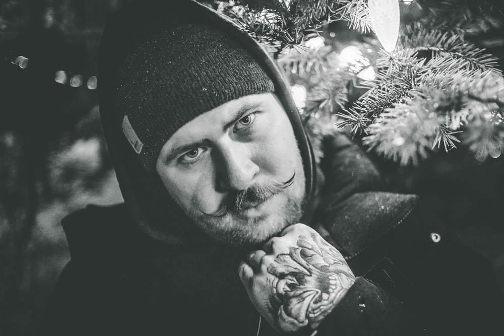 grayscale photo of man in beanie hat and hoodie