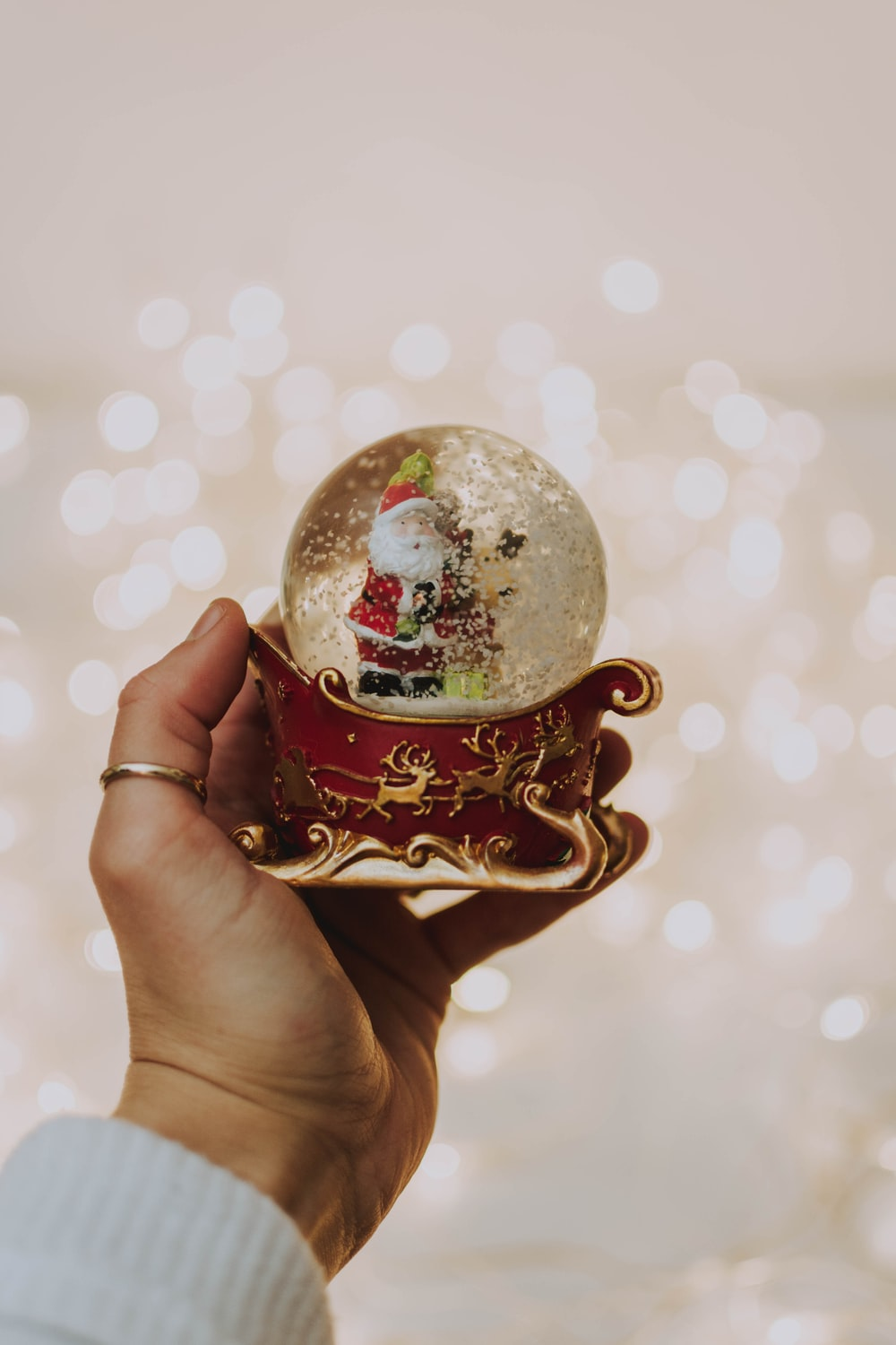 person holding Santa Claus snow globe