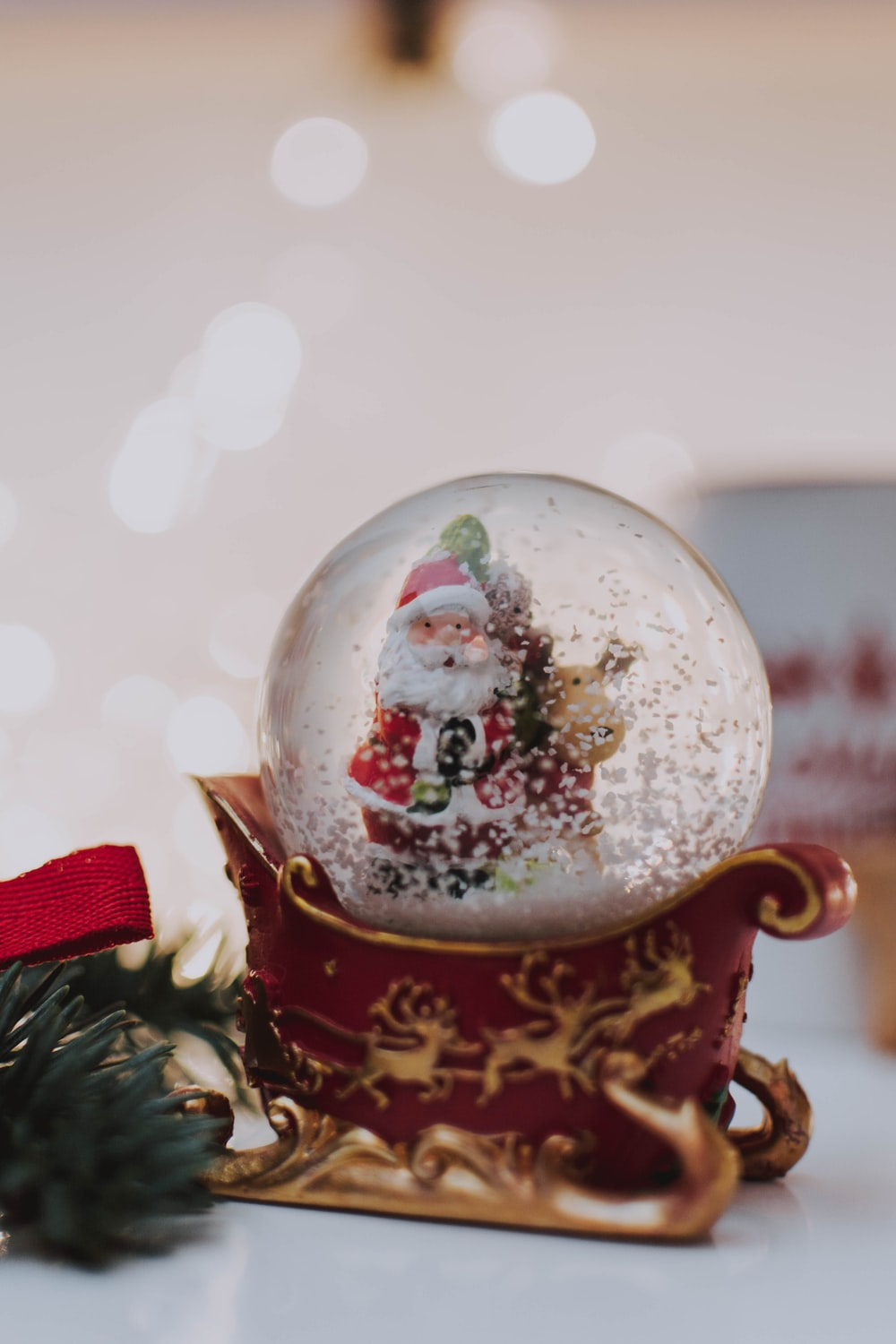Santa snow globe near green Christmas tree