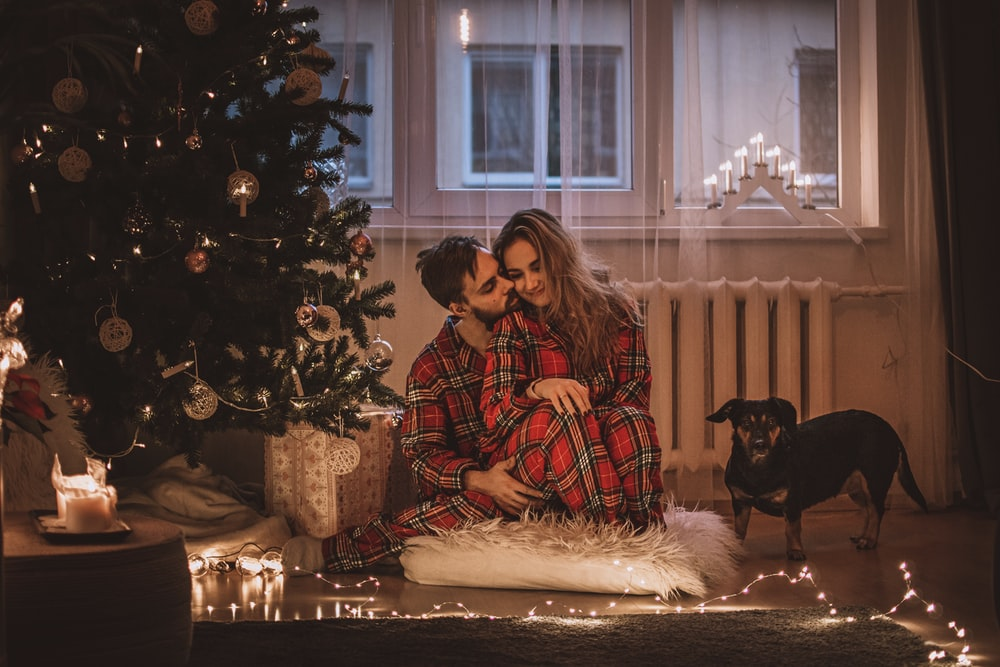 man and woman wearing matching pajamas sitting beside Christmas tree