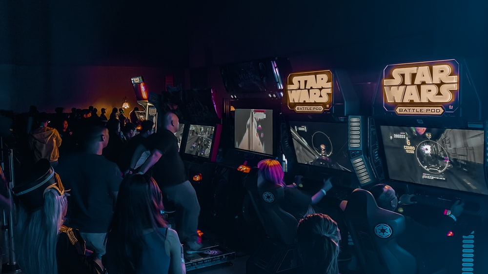 people inside building with Star Wars arcade machine