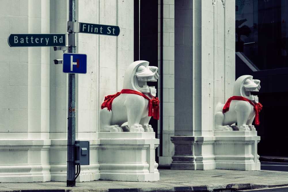 two dogs statue beside road sign