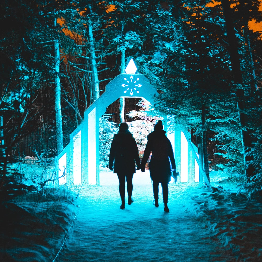 two persons walking in front of lighted arch at night