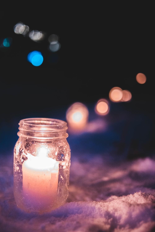 lit candle inside mason jar