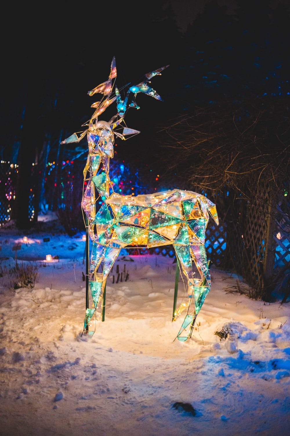 lighted deer ornament on snow at night