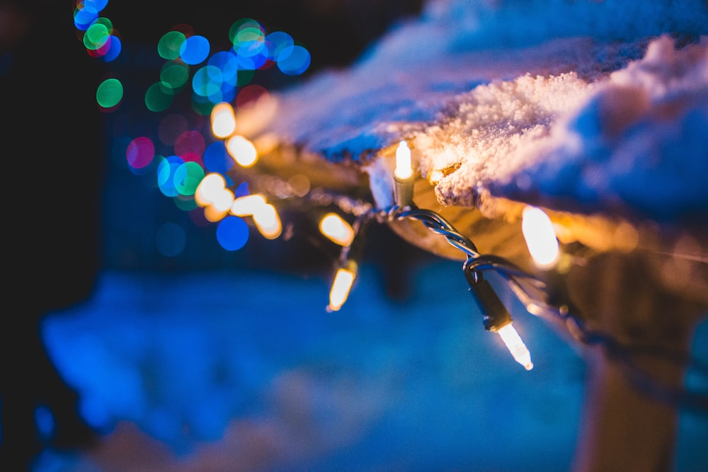 turned-on string lights on wooden rail with snow ]
