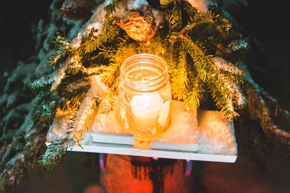 lit white candle in mason jar beside green plant at night