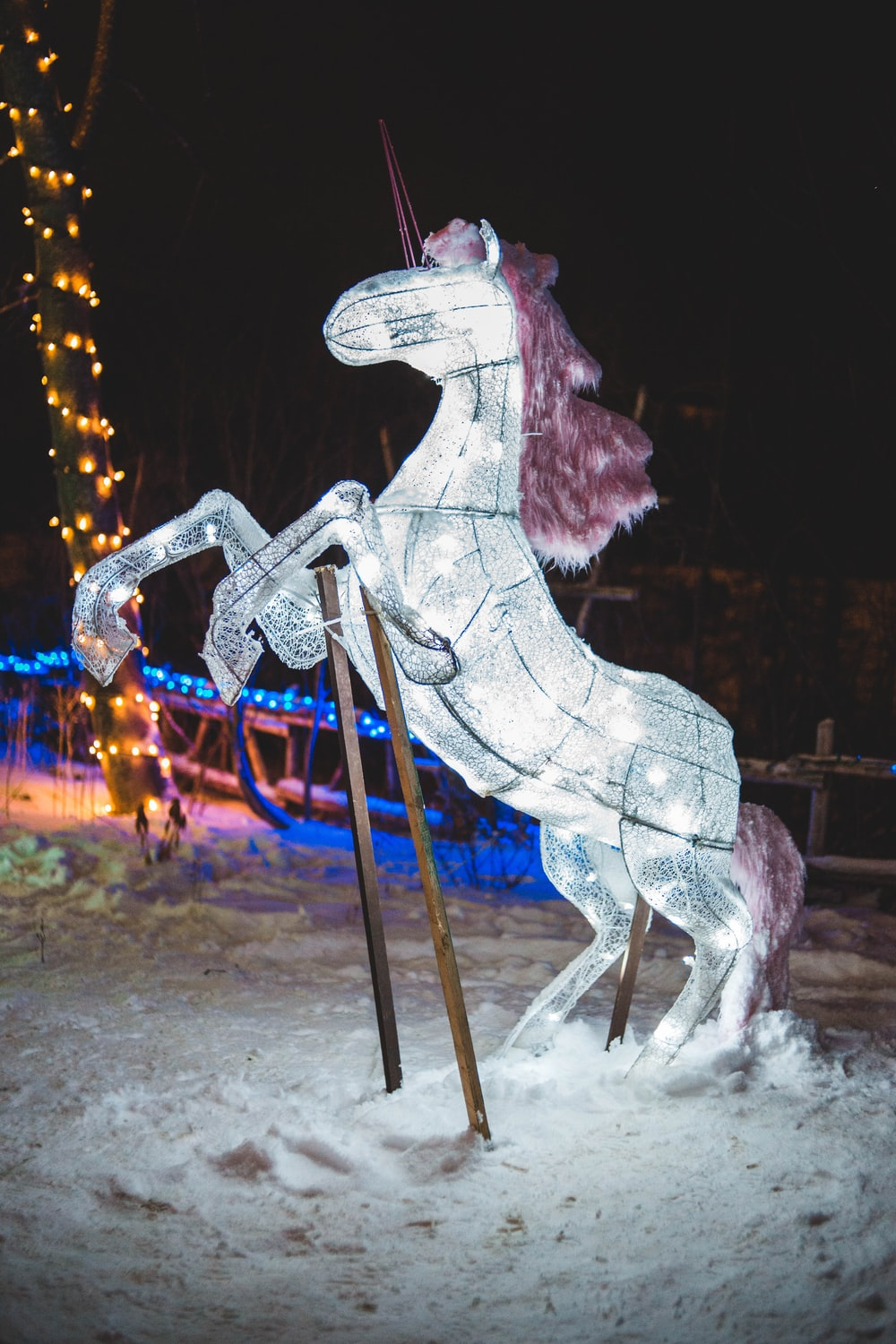 white rearing horse Christmas decor during night time