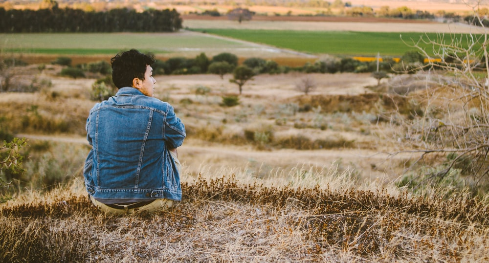 man wearing blue jacket sitting on the grass field