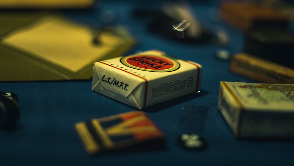 selective focus photography of cigarette boxes on blue table