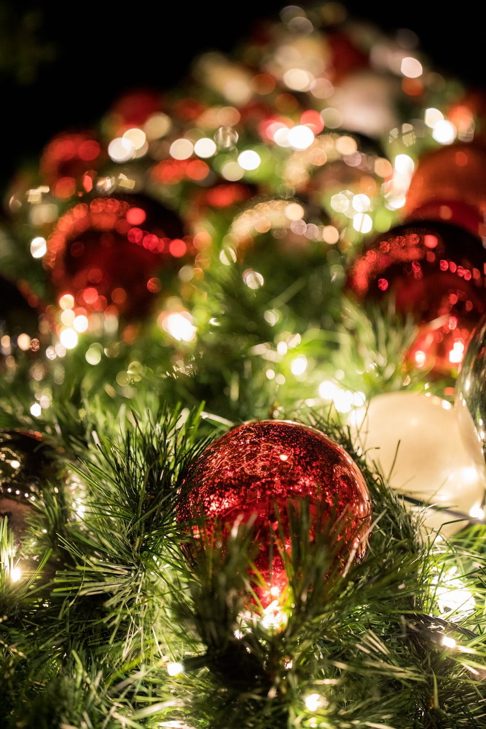 selective focus photography of red bauble on Christmas tree