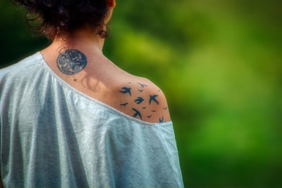 Tattooed woman in gray one-shouldered top