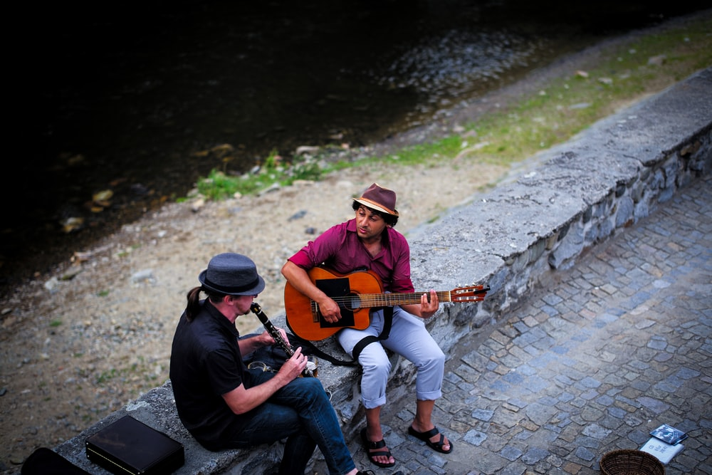 two men sitting on concrete barrier while playing instrument