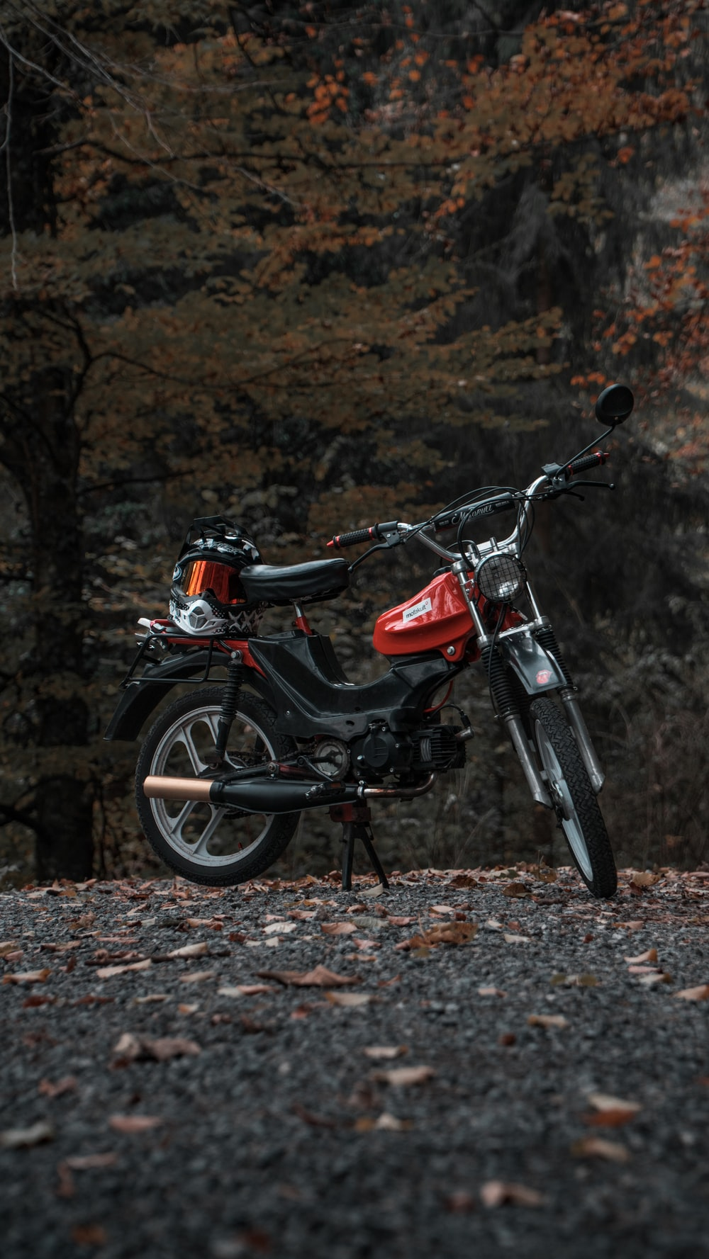 selective focus photography of parked black and red moped