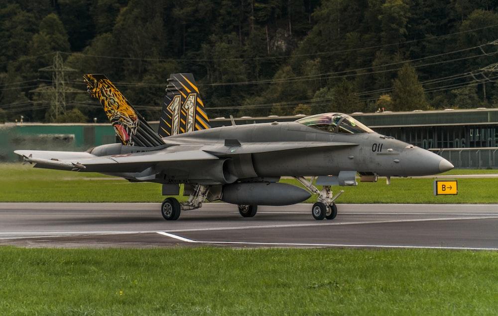 black fighter jet on gray asphalt road during daytime