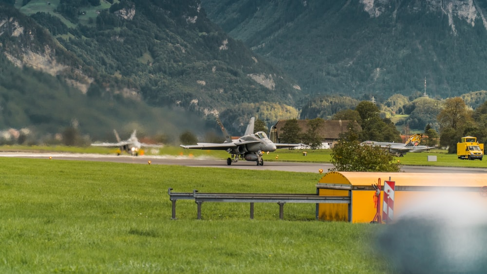 white and yellow plane on green grass field near mountain during daytime