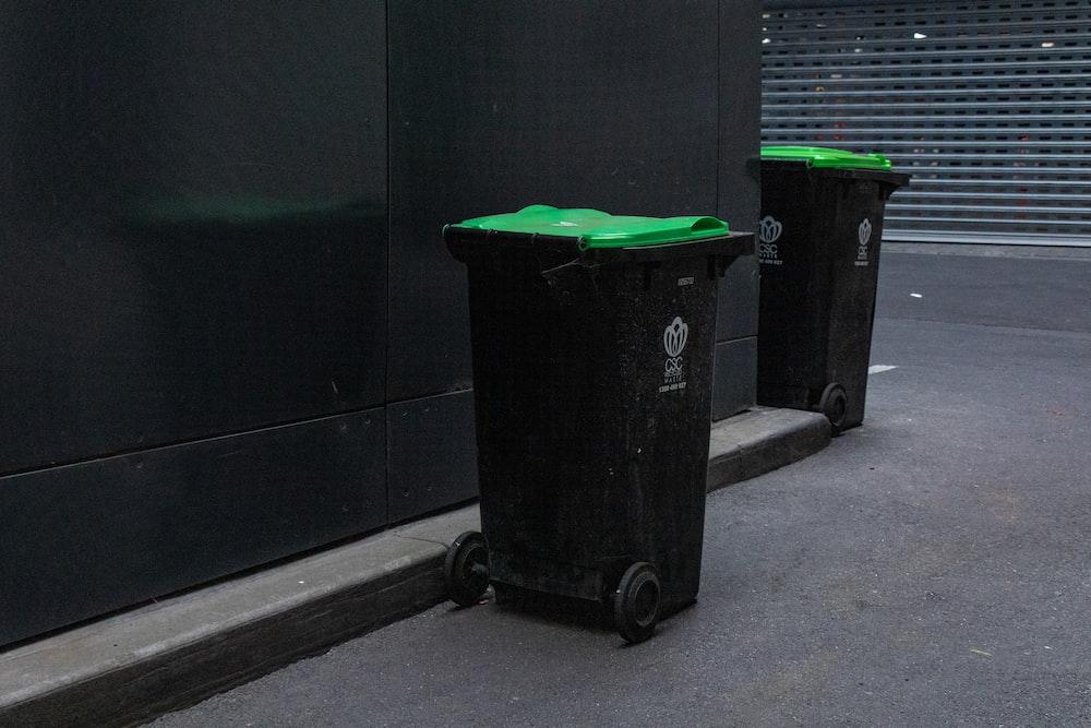 two black trash bins beside wall