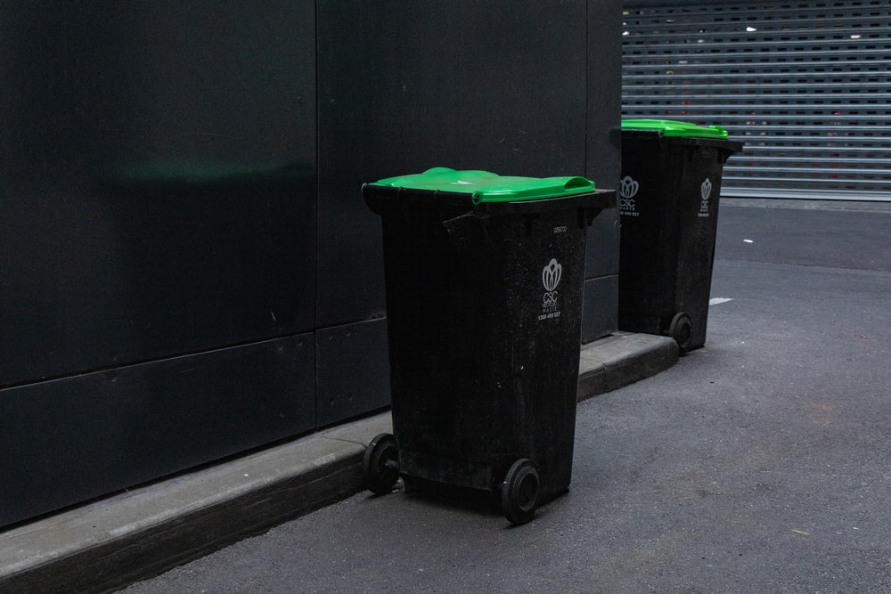 two black trash bins beside wall