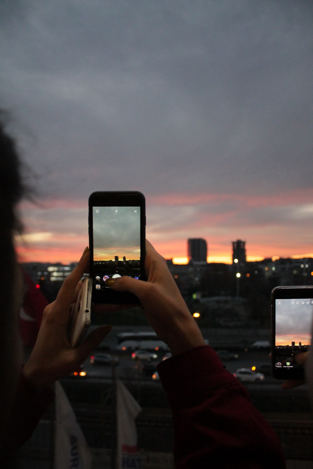selective focus photography of person taking photo of city during golden hour