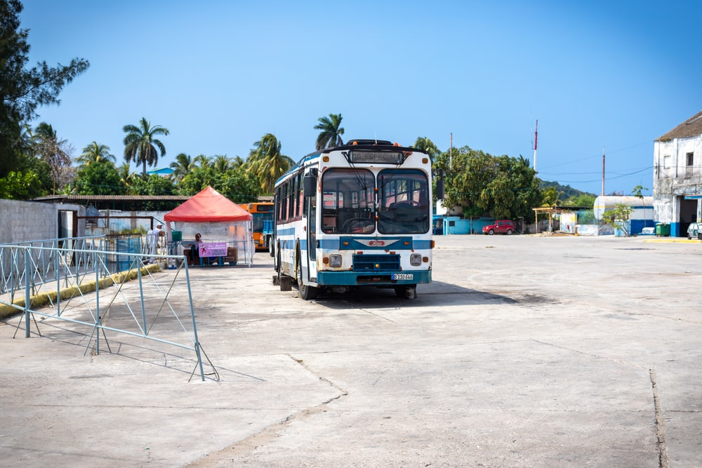 parked white and blue bus during daytime