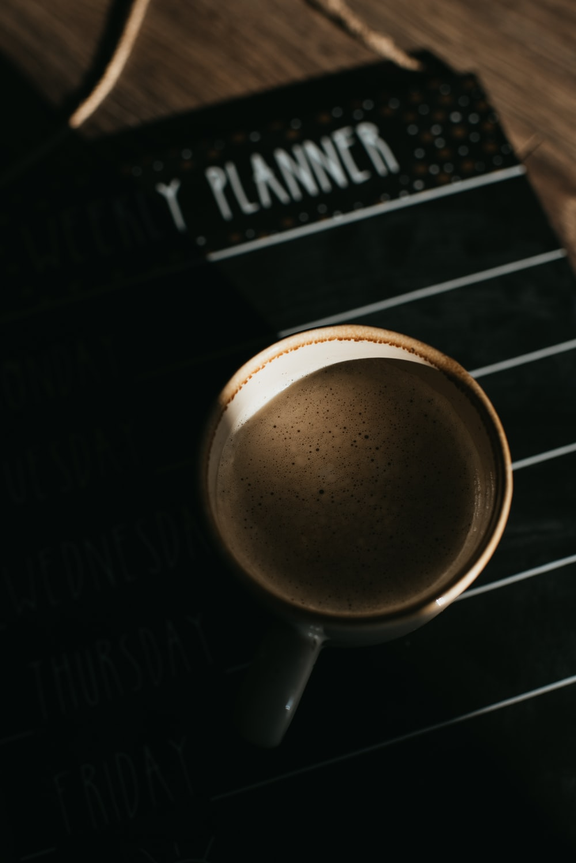coffee mug on top of planner
