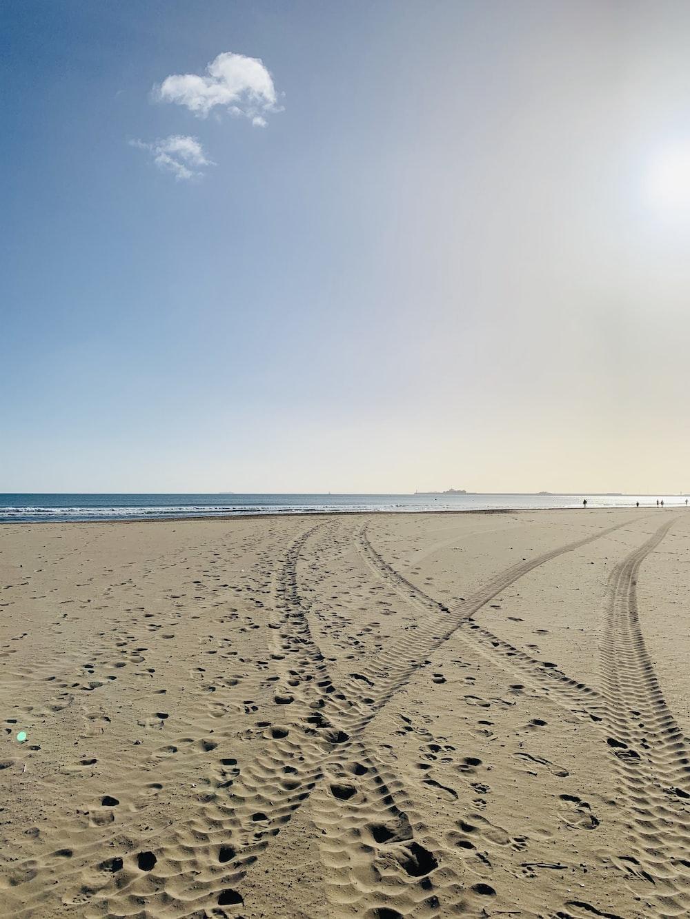 vehicle wheel mark on sand during daytime