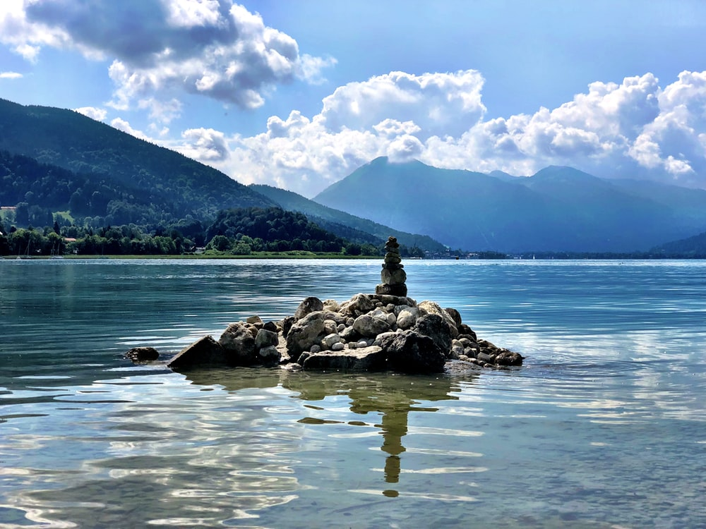 stack stones on body of water during daytime