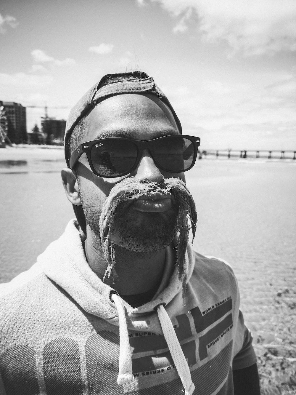 grayscale photography of man wearing Ray-Ban Wayfarer sunglasses