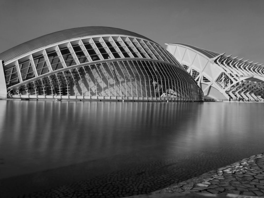 grayscale photography of building beside body of water during daytime