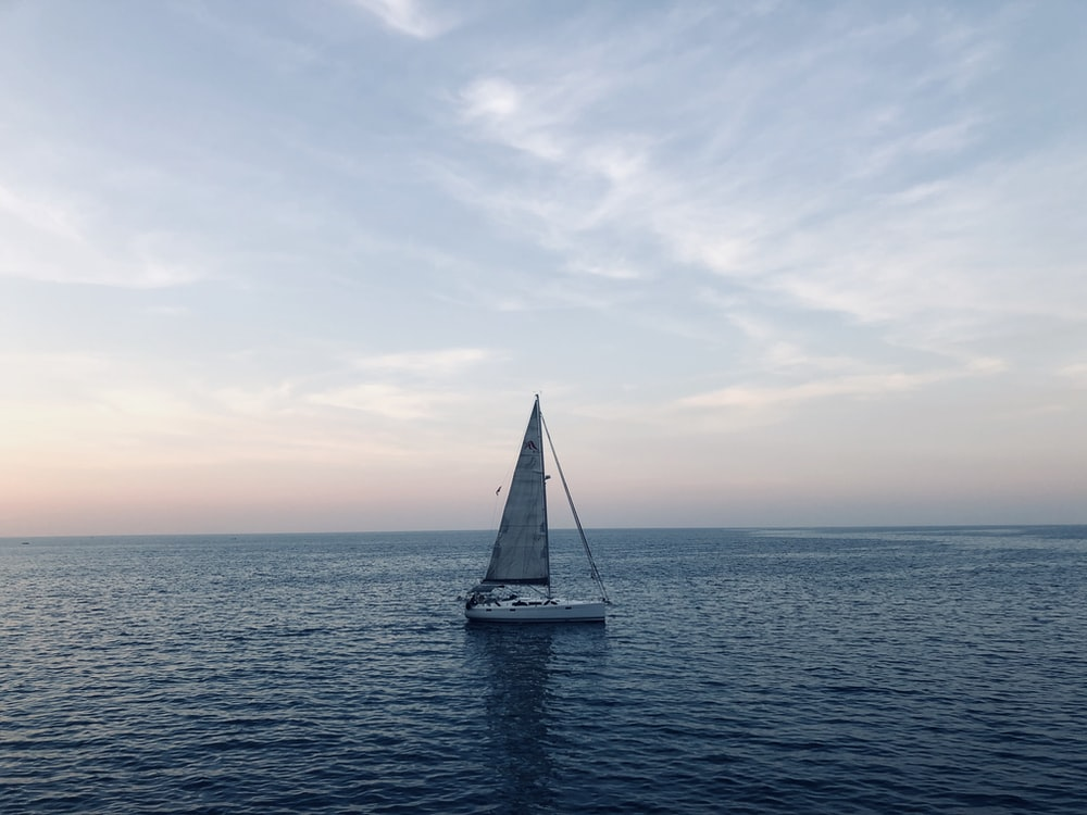 white sailboat on ocean under cloud ysky