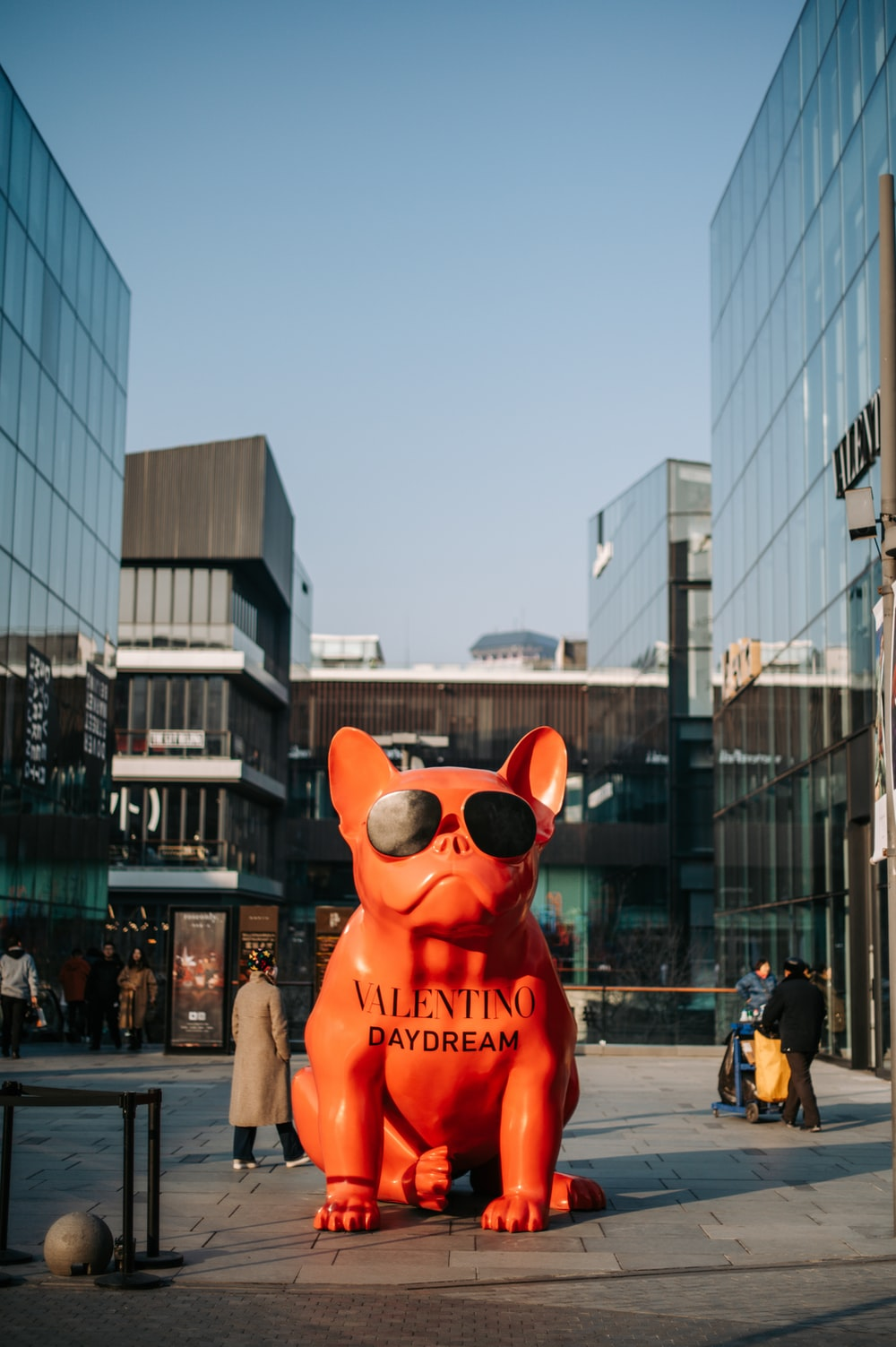 red dog statue beside glass building