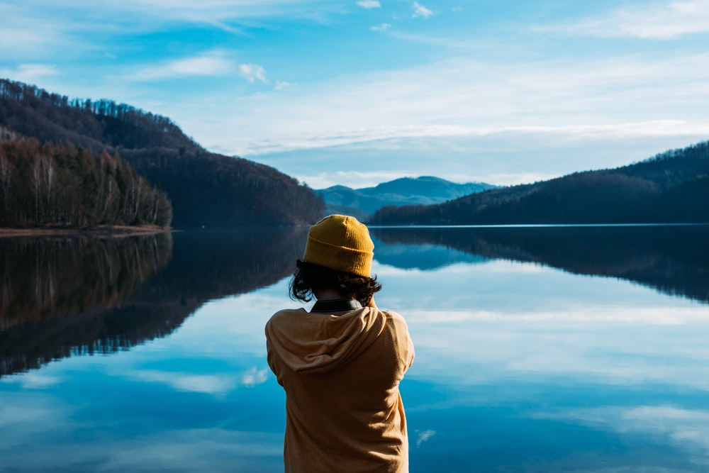 woman wearing yellow knit cap standing near the body of water