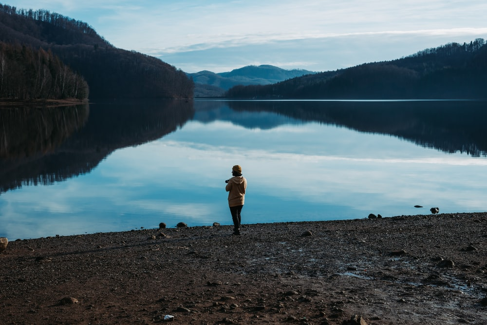 woman standing near the body of water photograph