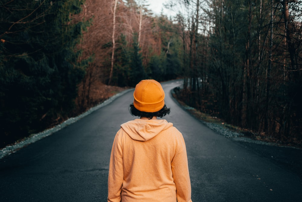 woman wearing yellow knit cap standing on the road