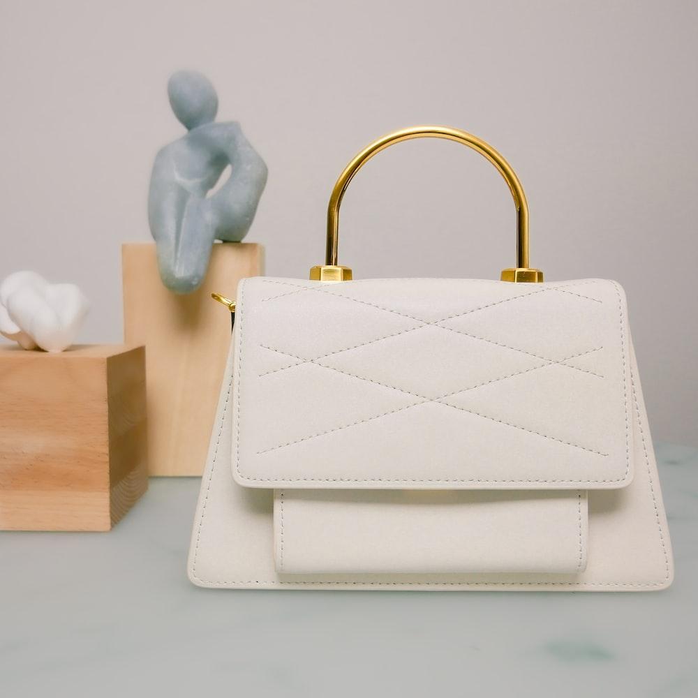 shallow focus photo of white leather handbag
