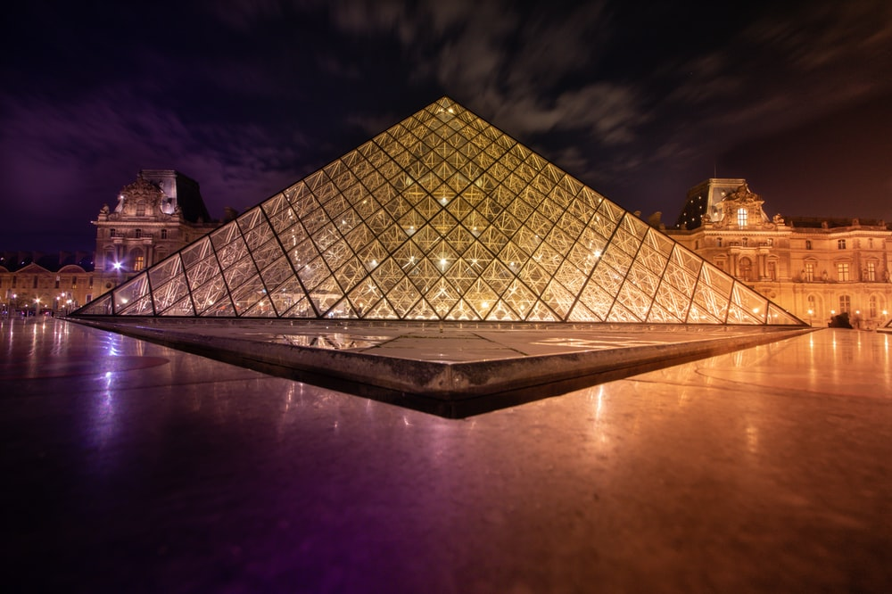 clear glass pyramid near buildings during night