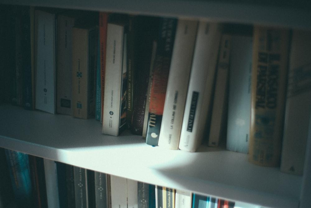 low-light photo of books on white shelves