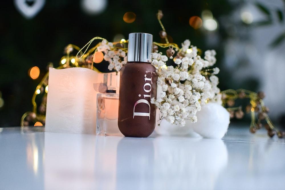 brown dior bottle beside flowers