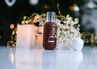 brown dior bottle beside flowers
