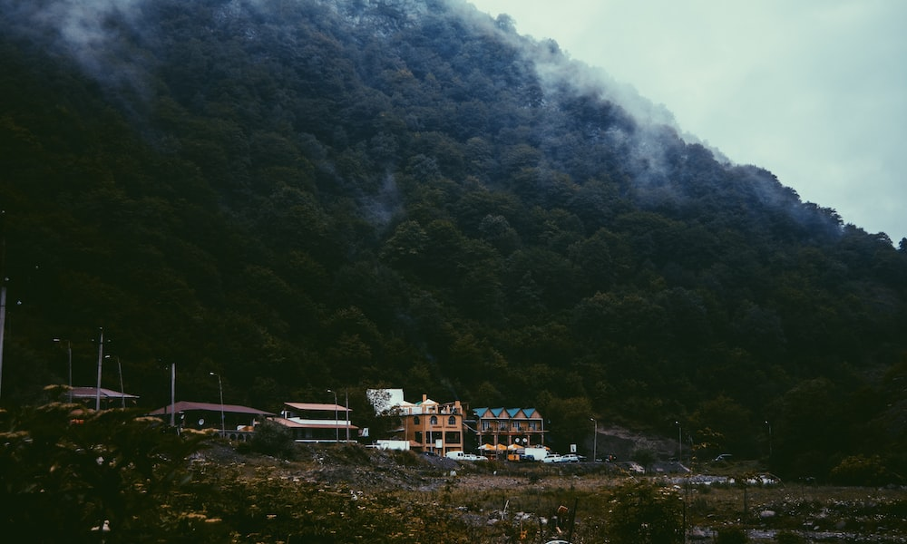 photography of buildings beside mountain during daytime