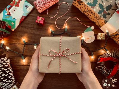 person holding brown box gift zoom background