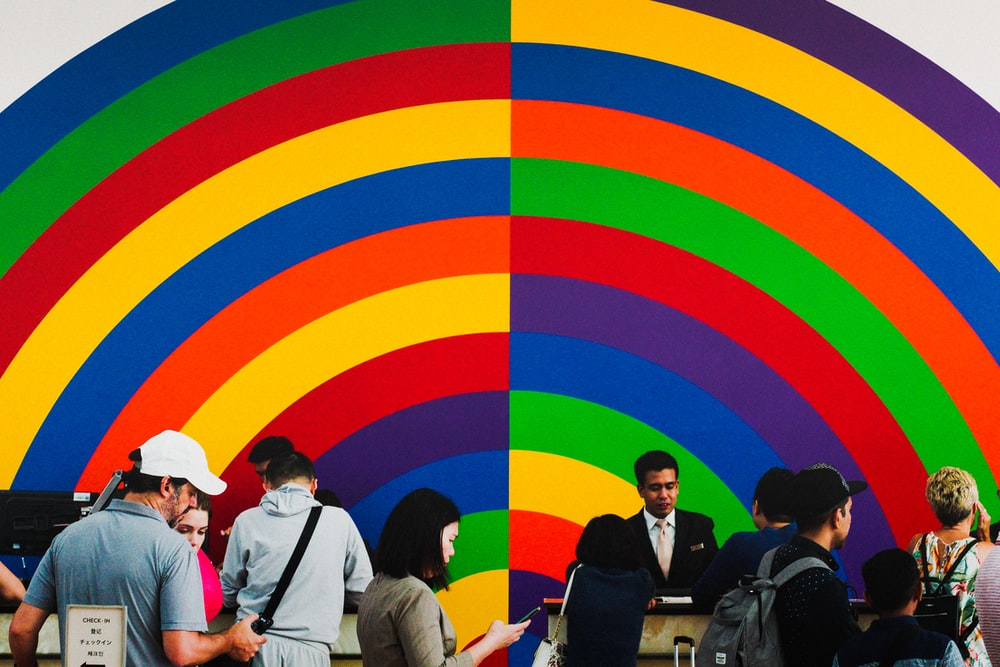 people standing beside multicolored wall