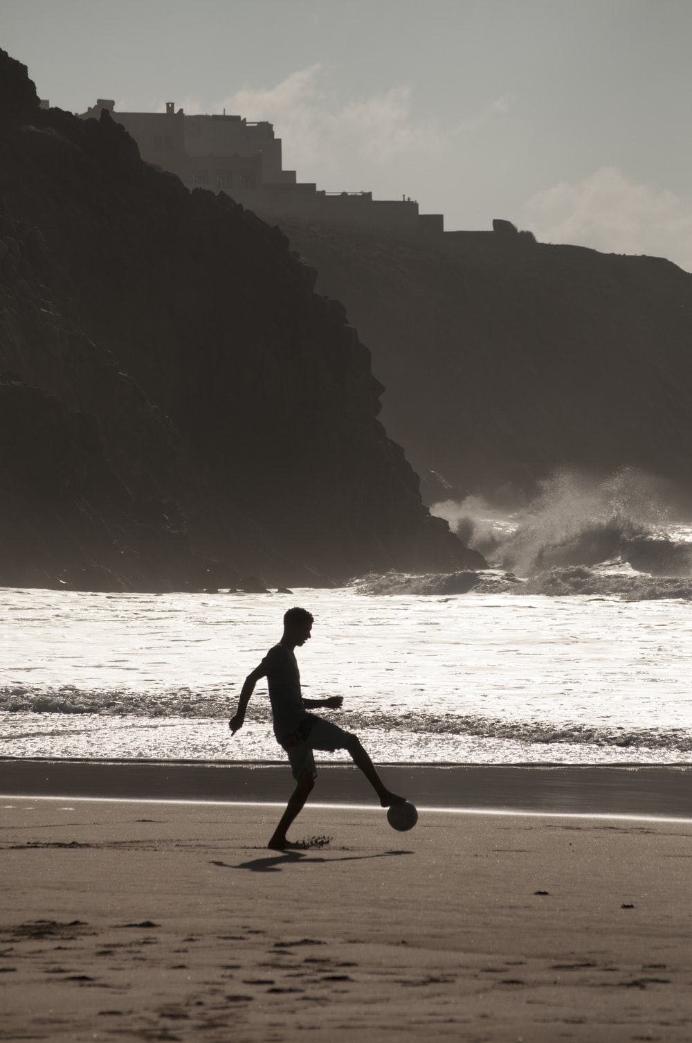 man playing soccer on shore