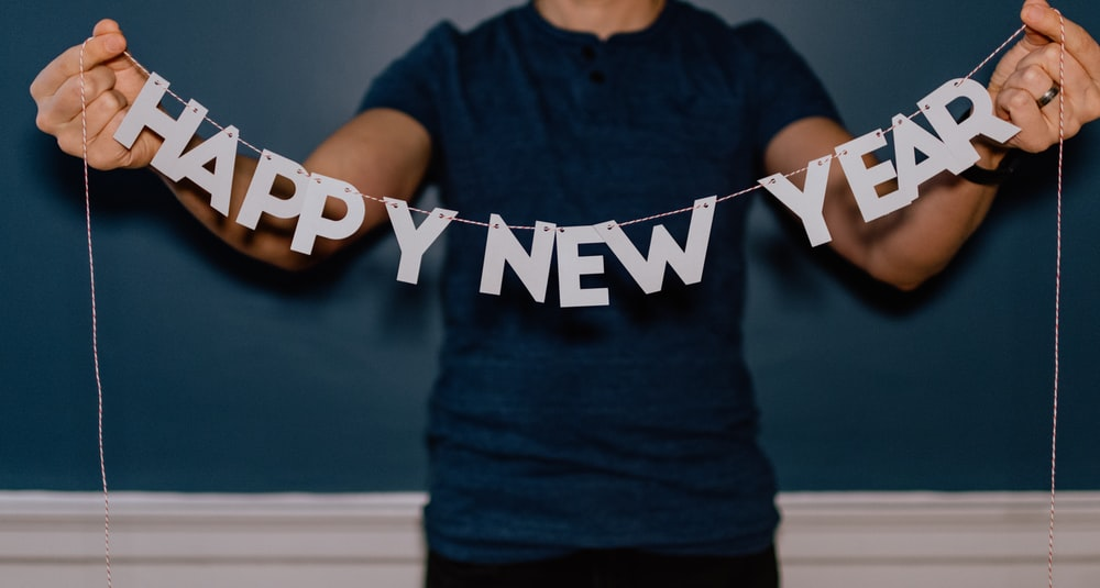 person holding happy new year decor