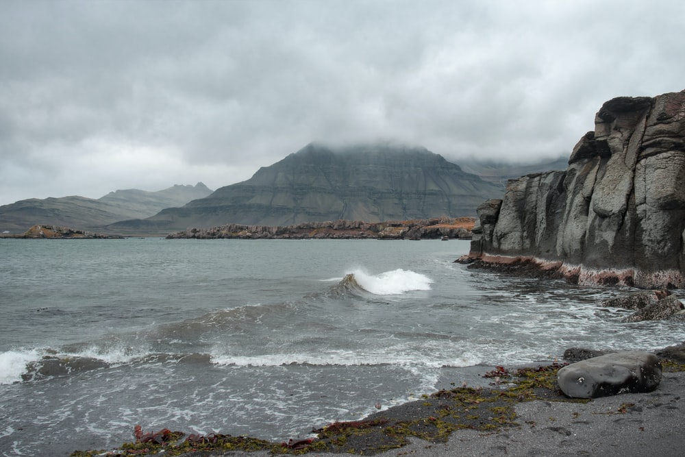 photography of seashore and mountain during daytime