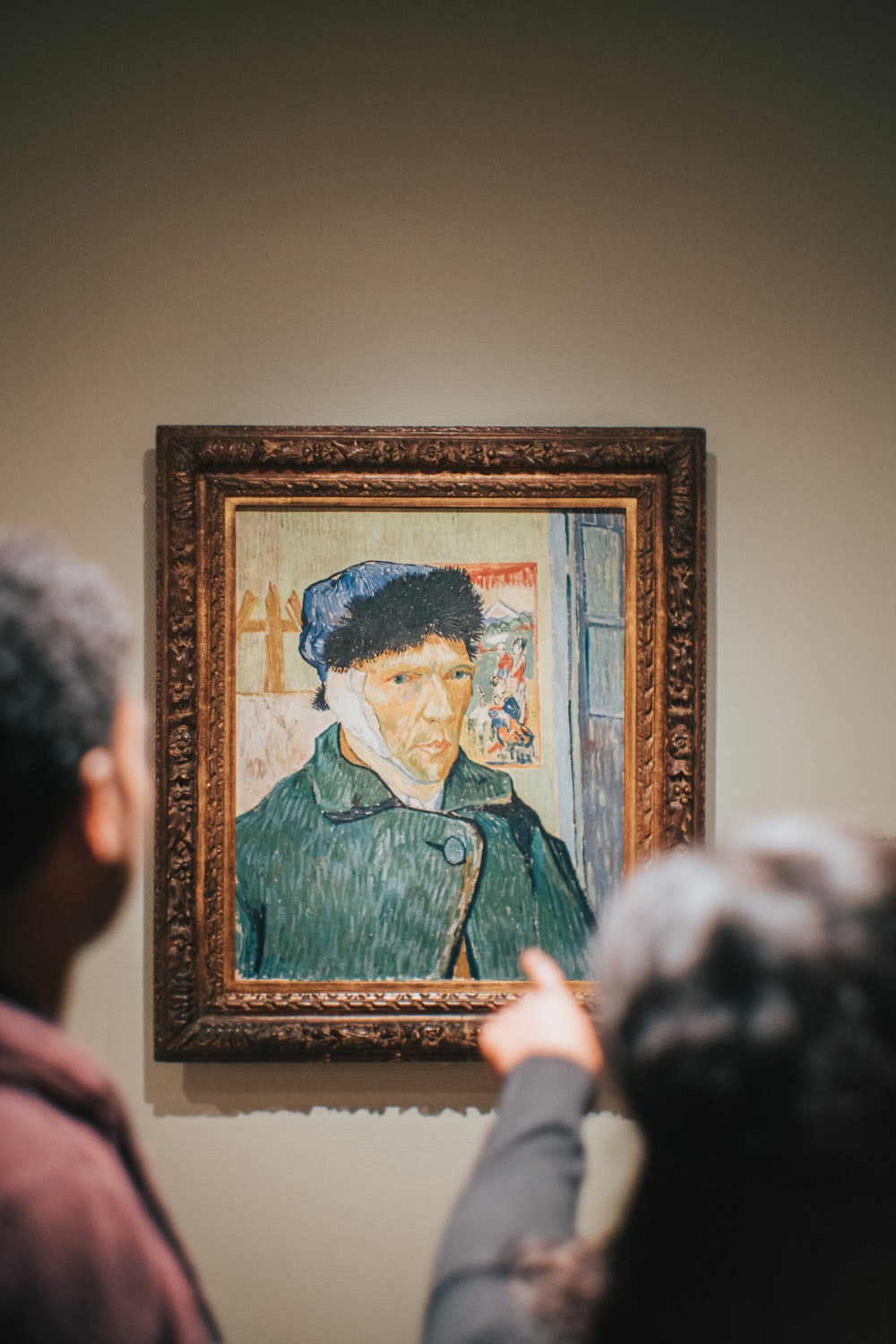 two person standing near Vincent Van Gogh Self-Portrait with Bandaged Ear