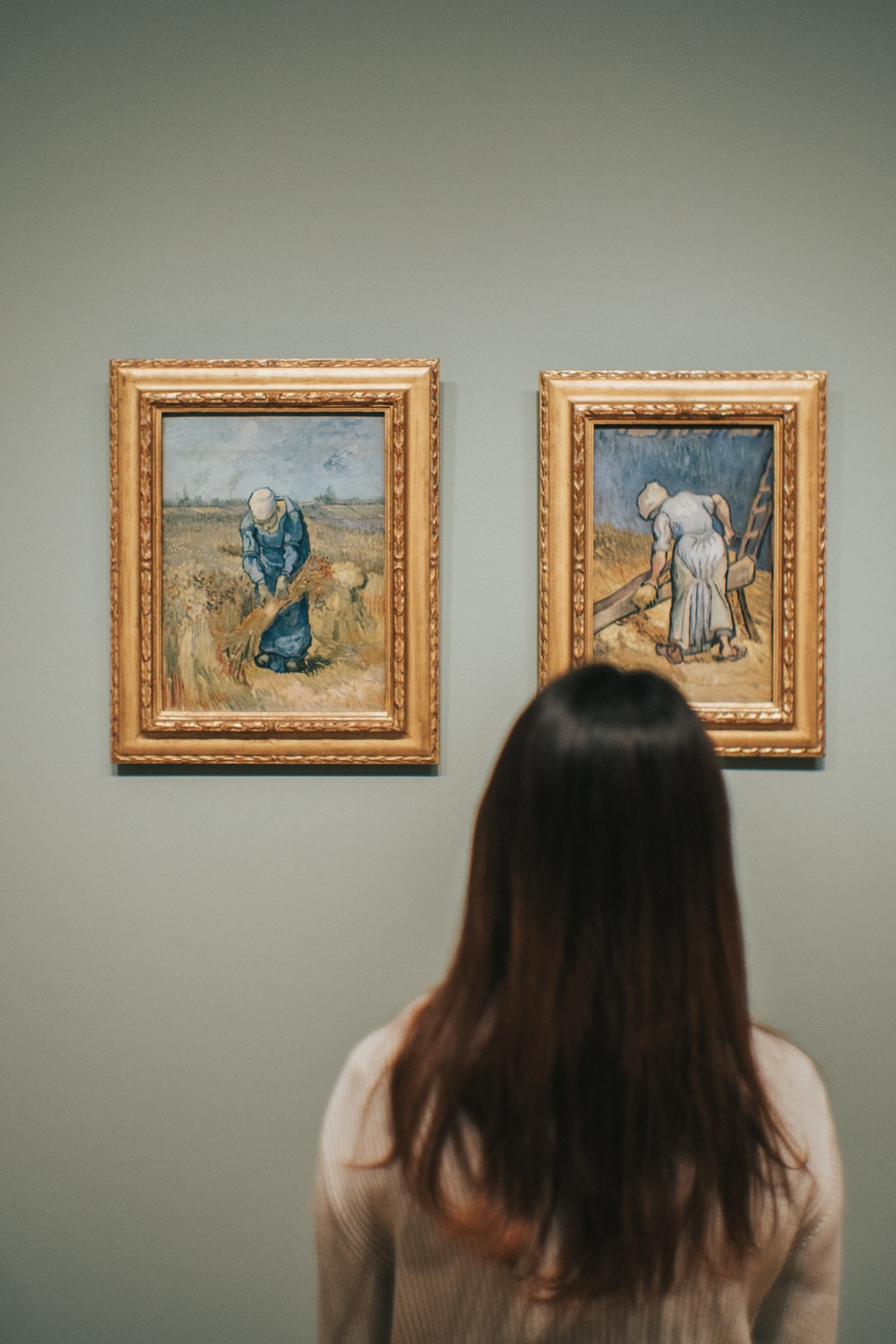 woman standing near Peasant Woman Binding Sheaves After Millet painting by Vincent Van Gogh