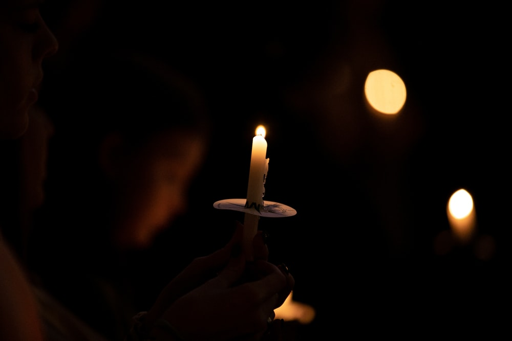 person holding lighted candle during nighttime