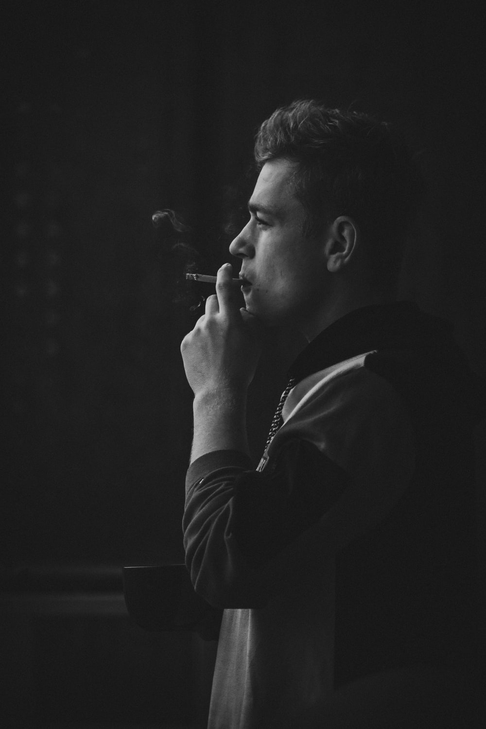 photography of man using cigarette