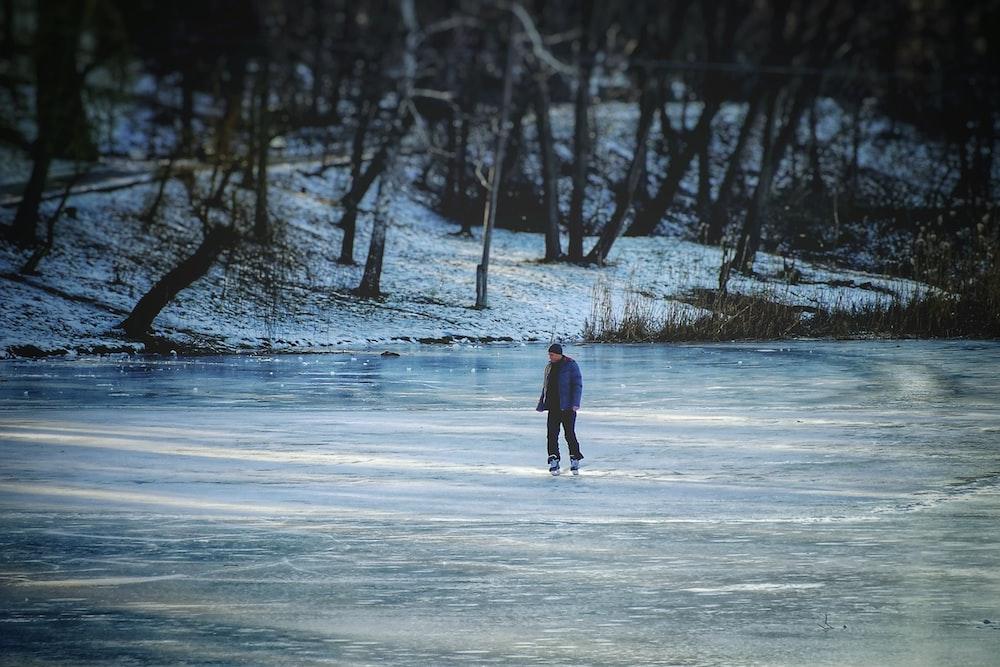 man skating n frozen lake